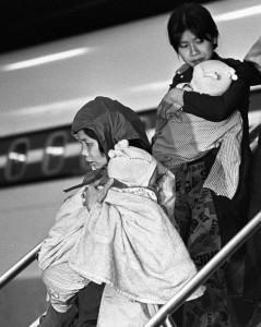 Two women getting off a plane carrying their young child
